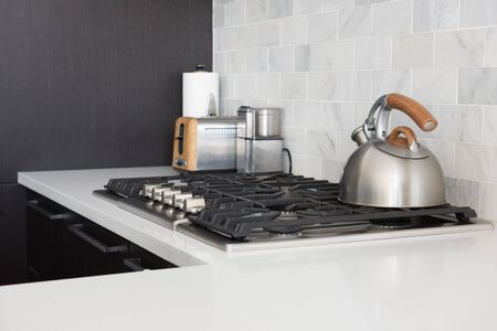 cooktop: The Image shows a fresh and elegant kitchen with a kettle on a oven with a white and gray background. Stock Photo