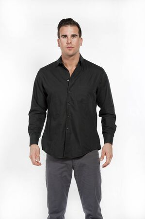 formal shirt: Attractive young white caucasian male model wearing a black formal shirt and gray pants posing in a studio on a white background while looking at the camera.