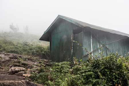 broken hill: An asbestos made hut on the rocky hills of Western Ghats in Kochi, on a foggy day. On the background, green trees and hillscape is seen. Stock Photo