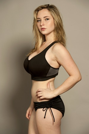 busty bra: Beautiful young female brunette looking at camera with straight hair in a studio setting while wearing black sports braw and black bottoms on a gray background.