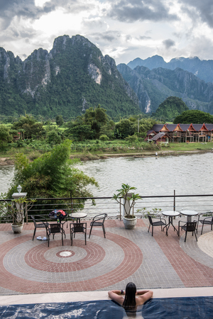 View of the Karst mountains from a hotel on the riverside in Vang Vieng. Vang Vieng is a riverside party town in Laos. The swimming pool of the hotel and tourists swimming are also seen.