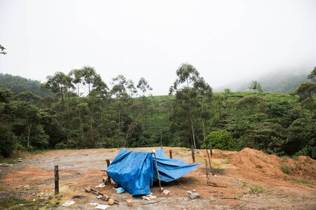 roughing: A blue colored abadoned tent on top of a hill in Rajamala at Kochi, Kerala. On the background, lush green hills and the clear white sky is seen on a sunny day. Stock Photo