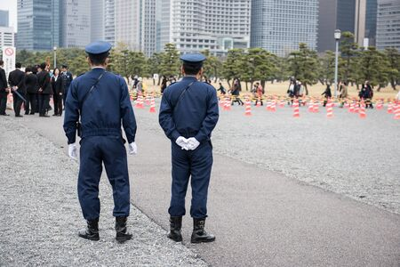 croud: Here in the image two on duty Japanese police officers standing and watching people to maintain law and order in the area. And few people can be seen standing in a queue in the picture.