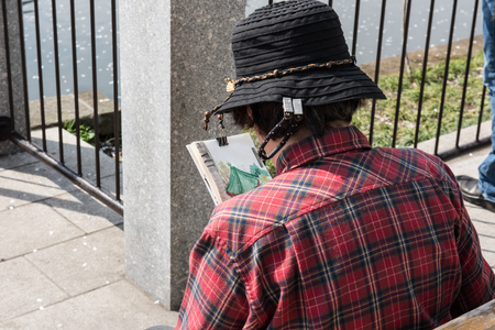 iron man: A local man sitting on a bench and reading newspaper during a sunny morning. He is seen wearing a black local made hat and a red shirt. On the background, an iron gate is seen. Stock Photo