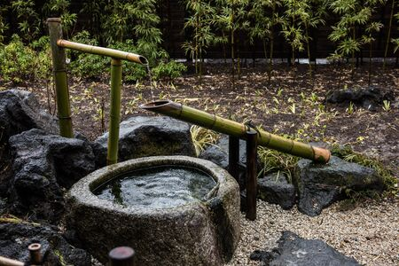 A water line system made of Bamboo sticks inside a garden in Japan. A well or water reservoir is also seen. On the background, green trees and the garden is seen.