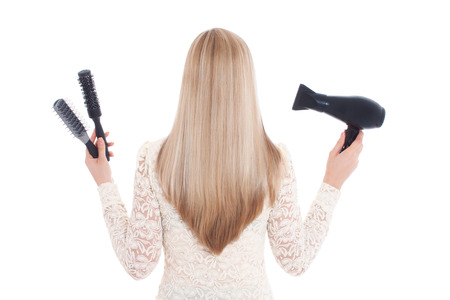 hairdryer: A blond woman on white background holding brushes in her left hand and a hairdryer in her right. She has beautiful, long and healthy hair. Stock Photo
