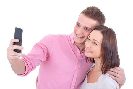 2 persons only: A young happy and beautiful couple taking a selfie with a smartphone.