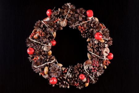 An original hand made christmas wreath on a black pine wood texture. Stock Image.
