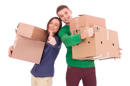 possibly: A young casually dressed couple holding cardboard boxes. Possibly moving to a new apartment or house together. Stock Photo