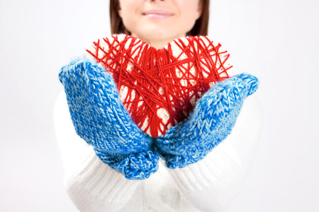 Beautiful young woman dressed in a warm white pullover giving a woven valentine heart. Holding it in blue winter mittens and smiling photo