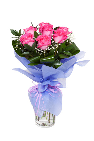 A bouqet of vivid pink roses in a clear glass vase isolated on white background. Possible gift for a valentine's day or a wedding anniversary Фото со стока