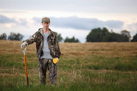 Man with metal detector and shovel posing in the field. Treasure hunter is wearing camouflage and has confident look Banque d'images