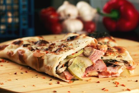 Calzone pizza rolls with ham and mushrooms. Shallow depth of field