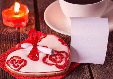 Romantic valentine's day dessert with an emty note, coffee cup and a candle. Surprise for a loved one. Shallow depth of field. Stock fotó