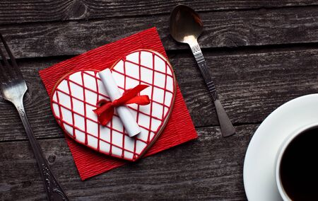 Beautiful red heart-shaped striped cookie with a surprise note on rustic wood. Valentine's day breakfast concept.