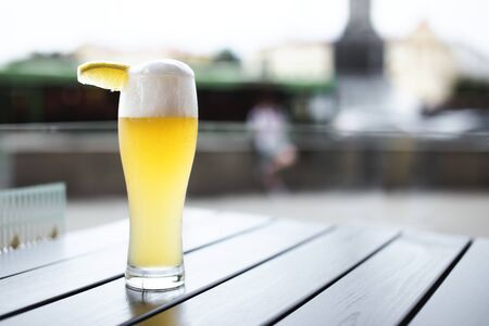 Glass of wheat beer with slice of lemon on a table outdoors in Minsk, Belarus