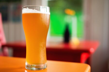 Pint of golden ale tapped craft beer on table in colorful bar. Vivid colors. Shallow depth of field Фото со стока