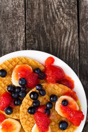 Tasty waffel with fruits banana, strawberry and blueberry.