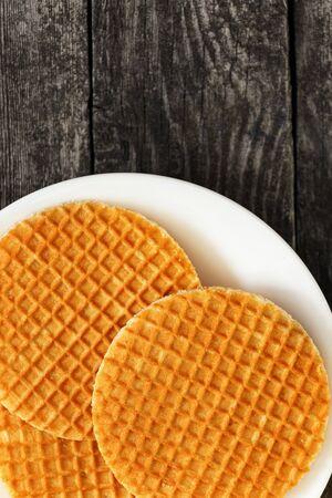 Waffles stroopwafel on a plate on dark wood. Sweet food for breakfast Фото со стока