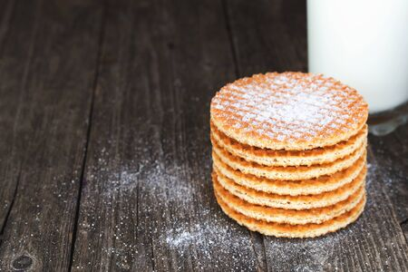 Stroopwafel waffles with milk on rustic wood. Shallow depth of field