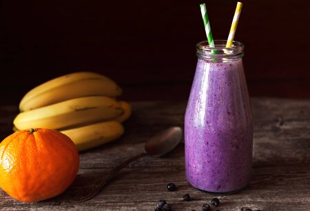 Fresh purple smoothie in a glass bottle made from bananas and blueberries. Shallow depth of field Фото со стока