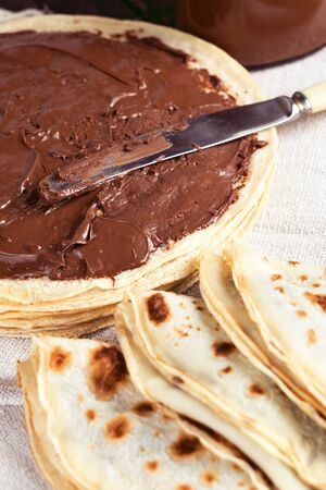 Tasty breakfast pancakes with milk chocolate spread. Shallow depth of field. Crepes with hazelnut sauce