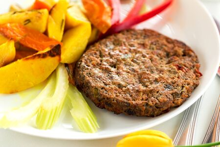 Tasty beef cutlet with potato and bell pepper on white plate