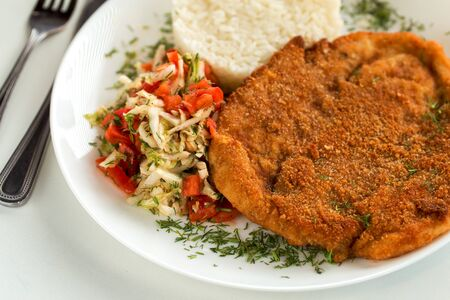 Austrian schnitzel with rice and cabbage salad on a white plate Фото со стока