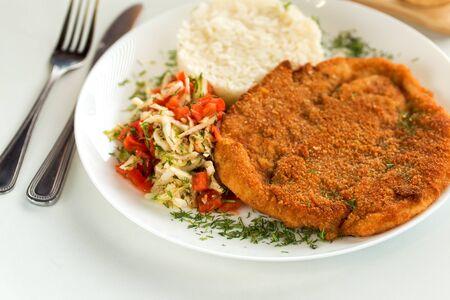 German pork schnitzel with rice and cabbage salad Фото со стока