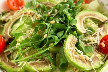 Tasty avocado and arugula salad close up. Delicious vegetarian salad