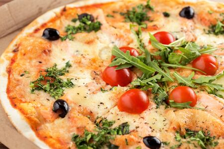 Tasty italian pizza in cardboard box close up. Pizza with seafood, salmon, tomatoes and arugula