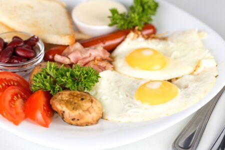 Tasty continental breakfast with eggs, sausage, bacon and mushrooms. Shallow depth of field