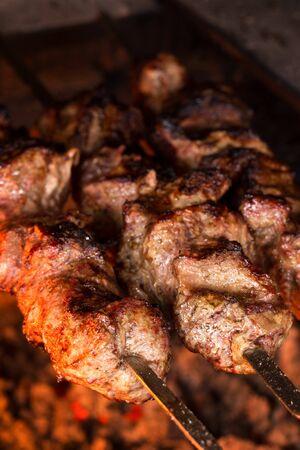 Meat grilled on charcoal. Pork bbq on skewers. Shashlik close up