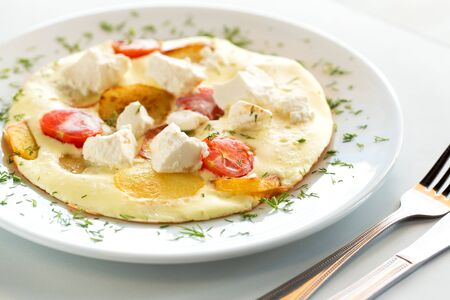 Tasty omelette with tomato, cheese and potato on white plate Фото со стока