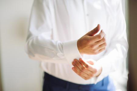 cufflink: A groom fastening a cuff-link before getting married