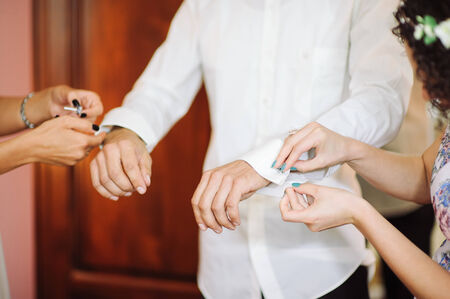 cuff link: A groom fastening a cuff-link before getting married