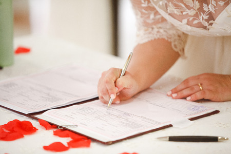 marriage certificate: bride signs marriage certificate with a pen Stock Photo