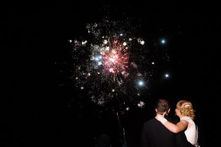 花嫁および新郎と暗い空を背景に色鮮やかな花火のクラスター