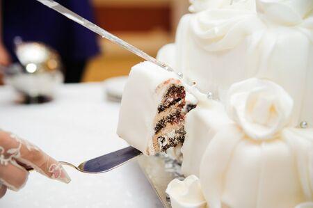 boda pastel: la novia y el novio est�n cortando el pastel de boda en la recepci�n Foto de archivo