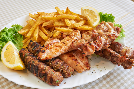 assort: Assort of Grilled sausages with fries and vegetables, barbecue Stock Photo