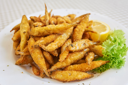 whitebait: Small fried fish, A small dish of fried whitebait with slices of lemon. This would be served as a starter or tapas in Spain.
