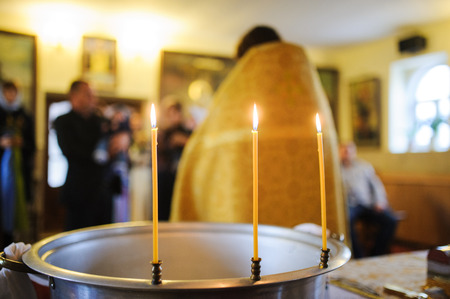credo: three burning thin candle during christening  baptism