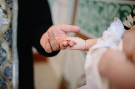 christian candle: holding baby hand during christening Orthodox baptism Stock Photo