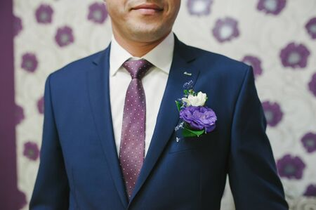 boutonniere: Pinning a Boutonniere for groom on wedding day