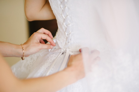 getting dressed: bride getting dressed on her best day ever