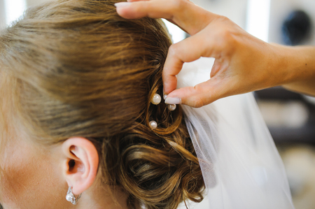 bride get a professional hair style at beauty salon