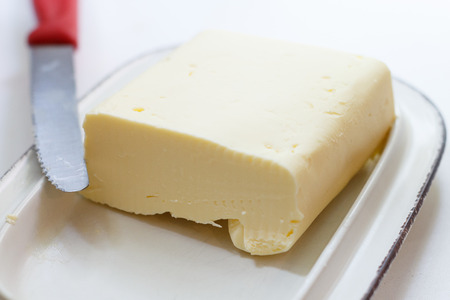 Pat of fresh farm butter on a butter dish with a knife