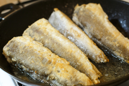 Fried hake fish fillet in a frying pan at kitchen
