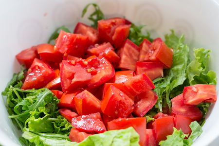 Healthy green salad, tomatoes in white bowl