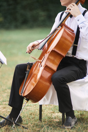 Young man playing cello outside. Cellist playing classical music on cello